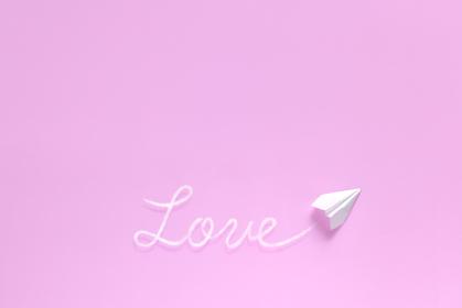 飛行機雲で文字を書く紙飛行機 1 love ピンク背景