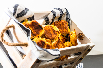 Freshly baked homemade ham and cheese puff pastry in a rustic crate. , Romania, Bucharest, Bucharest