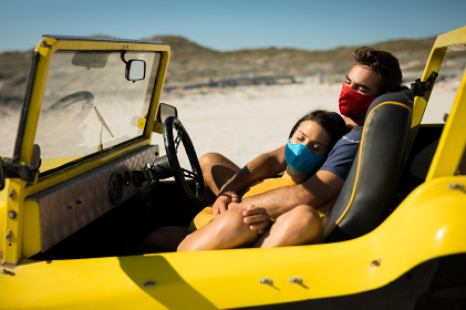 Happy caucasian couple wearing face masks sitting in beach buggy relaxing. beach stop off on summer holiday road trip during coronavirus covid 19 pandemic.