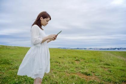 草原でタブレットを見る日本人女性