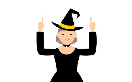 ハロウィンの仮装、魔女姿の女の子が両手で指さしをするポーズ