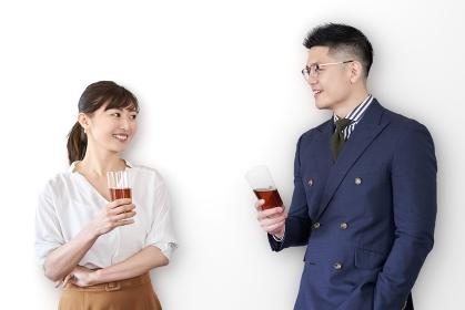 交流会でグラスを持ち、話をするアジア人ビジネスパーソン
