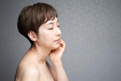 頬に手を当てて横を向く中年の日本人女性