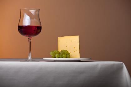 テーブルの上の赤ワインとチーズと葡萄