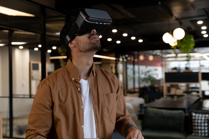 Mixed race businessman wearing virtual reality headset in creative office. technology and social distancing in business office workplace during covid 19 coronavirus