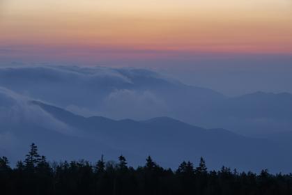 峠の向こうに広がる風景ががオレンジと紫、青に明るくなり、夜明けが迫る