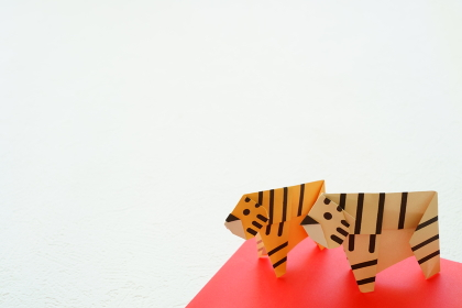 年賀状に使える白い背景に折り紙の左を向いた2頭の黄色い虎とホワイトタイガー