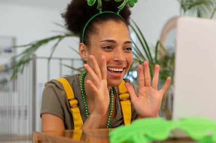 Happy mixed race woman celebrating st patrick's day making video call and waving. staying at home in isolation during quarantine lockdown.