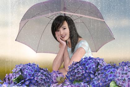 梅雨の雨が降る中女性が傘をさしてしゃがみこみアジサイとカタツムリを楽しそうに眺める