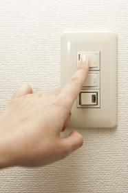 電気をつける女性