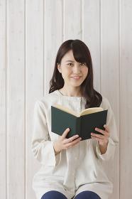 開いた本を持っている日本人女性