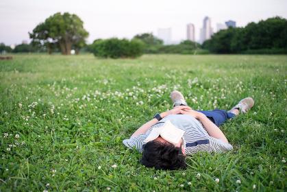 芝生で寝る男性(文庫本・日よけ)