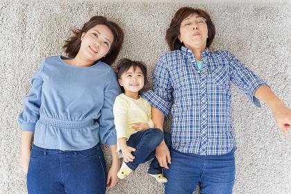 部屋で寝転ぶ子供と母とおばあちゃん