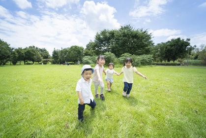 青空の下、手を繋いで元気に歩く子供たち