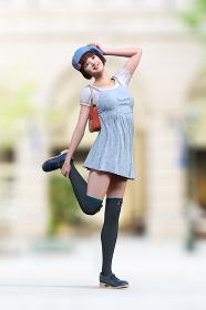 ピンクのリボンがついた青いベレー帽をかぶったボブヘアの笑顔の女子片足を持ち上げているポーズ