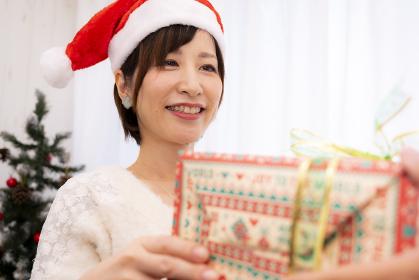 クリスマスプレゼントを手渡す女性【2020】