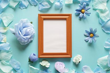 青を基調とした造花と背景。中央に縦長の木製フォトフレームの中に白いコピースペース。平置きの俯瞰撮影。