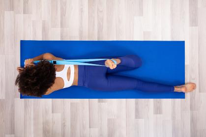 Woman Using Yoga Belt While Doing Exercise