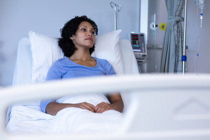 Mixed race female patient sitting up in hospital bed looking away in thought. medicine, health and healthcare services.