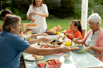 Front view of a multi-generation Caucasian family sitting outside at a dinner table set for a meal, talking and serving food. Family enjoying time at home, lifestyle concept