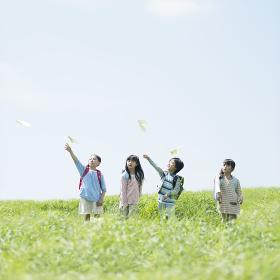 草原で紙飛行機を飛ばす小学生