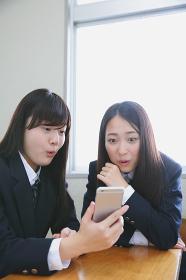 スマートフォンを見る女子高生