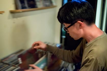 レコード店でレコードを探す男性