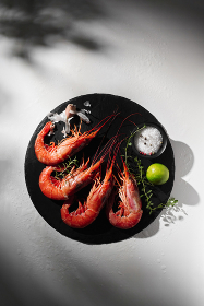 Raw red prawns with condiments on grey background with shadow