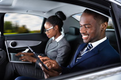 Two Businesspeople Sitting Inside Car Using Electronic Devices