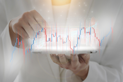 タブレットPCを操作する女性と株価チャートの合成写真