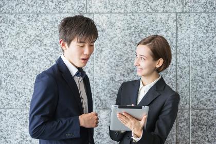 タブレットPCでミーティングをする外国人の男女(国際化イメージ)