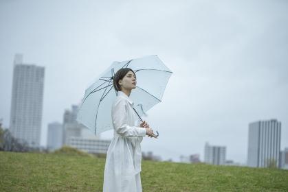 雨の中傘を挿して佇む白いワンピースを着た若い女性