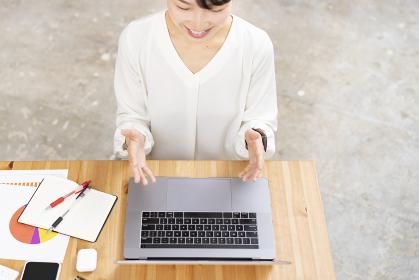 パソコンの画面に向かって話しかける女性