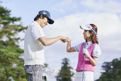 ゴルフ グータッチをする日本人カップル