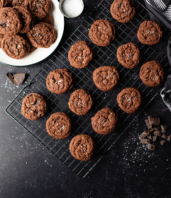 Overhead view of salted dark chocolate cookies on black counter.