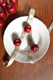 姫リンゴと金色のリボンで皿を飾り付ける 1 縦位置