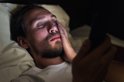 Bearded caucasian male is watching something on his mobile phone