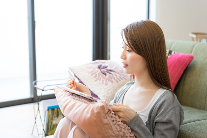 タブレットPCでネットショッピングの決済をする女性