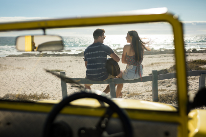 Happy caucasian couple next to beach buggy by the sea playing guitar. beach break on summer holiday road trip.