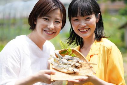 鮎の塩焼きを持つ女性