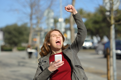 Excited teen celebrating online news in the street