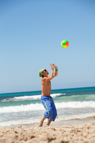 adult young sporty man is playing beach volleyball