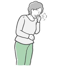 口を手で押さえて咳をする長袖を着た中年女性