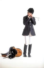 Portrait, Ganzfigur, Maedchen, Reiterin, 12 Jahre, mit schwarzer Reitjacke, weisser Hose und Reitstiefeln, Gerte in der Hand, befestigt ihre Reitkappe