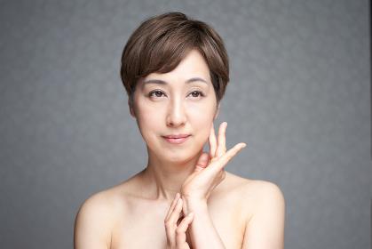 頬に手をあてる中年の日本人女性