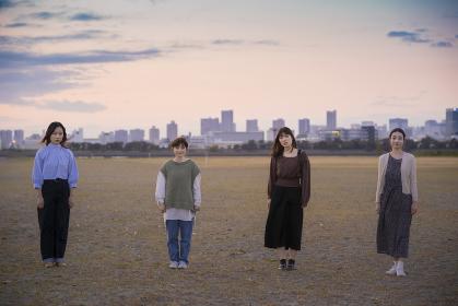 夕暮れの中、少し距離を空けて立つ若い女性4人