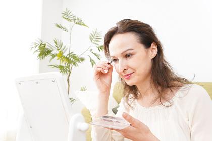 自宅で化粧をする若い女性