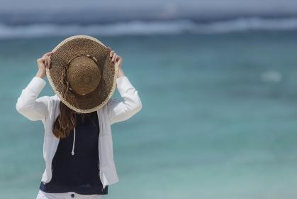 麦わら帽子で顔を隠す日本人女性