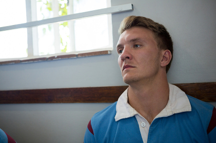 Close up of thoughtful rugby player sitting against wall