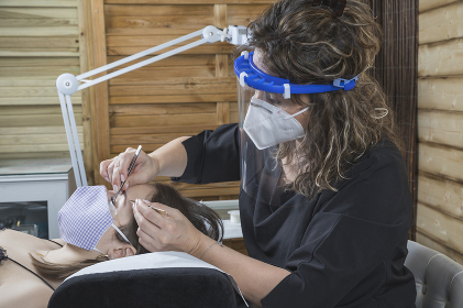 beautician working with mask and protective screen for the virus COVID